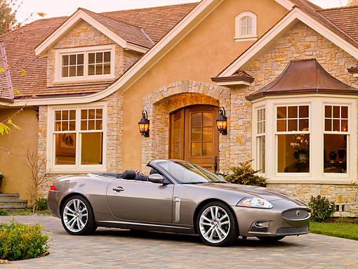 AUT 12 RK0290 01 © Kimball Stock 2009 Jaguar XKR Convertible Gray 3/4 Front View On Driveway By House