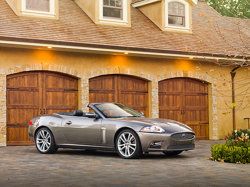 AUT 12 RK0291 01 © Kimball Stock 2009 Jaguar XKR Convertible Gray 3/4 Front View On Driveway By House
