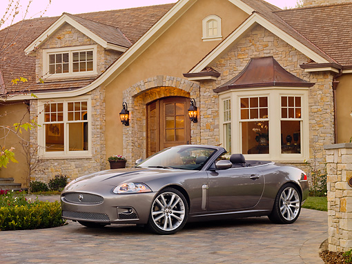 AUT 12 RK0292 01 © Kimball Stock 2009 Jaguar XKR Convertible Gray 3/4 Front View On Driveway By House