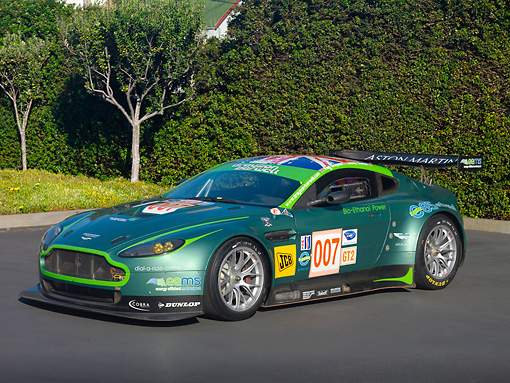 AUT 13 RK0270 01 © Kimball Stock 2007 Aston Martin DBR9 Race Car 007 Green 3/4 Front View On Pavement By Shrubs