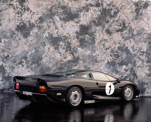 AUT 13 RK0026 11 © Kimball Stock Jaguar XJ220 Racing Car Black 3/4 Rear View On Black Floor Gray Marble Background Studio