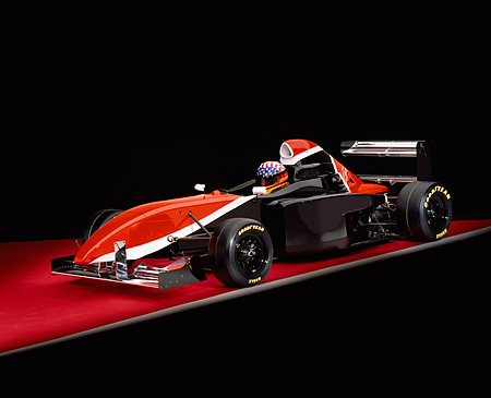AUT 13 RK0160 01 © Kimball Stock 2006 Mazda Pro Formula Race Car With Driver Black Orange And White Front 3/4 View On Red Floor Studio