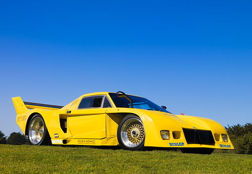 AUT 13 RK0205 01 © Kimball Stock 1977 De Tomaso Pantera Class C Yellow Front 3/4 View Low Angle On Grass Blue Sky