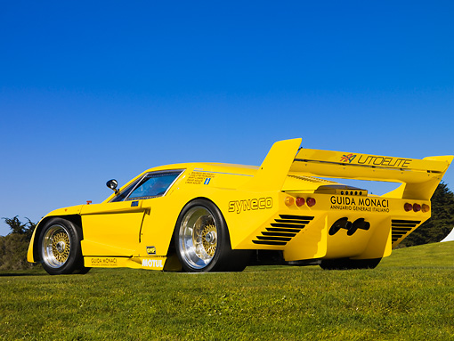 AUT 13 RK0209 01 © Kimball Stock 1977 De Tomaso Pantera Class C Yellow Rear 3/4 View Low Angle On Grass Blue Sky