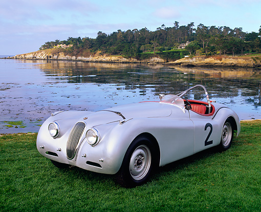 AUT 13 RK0268 01 © Kimball Stock Jaguar XK120 Competition Roadster Silver 3/4 Front View On Grass By Ocean