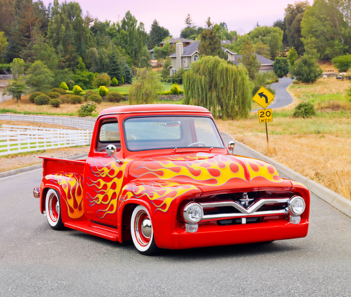 AUT 14 BK0040 01 © Kimball Stock 1954 Ford F-100 Pickup Truck Hot Rod Red With Flames 3/4 Front View On Pavement By Fence And Trees