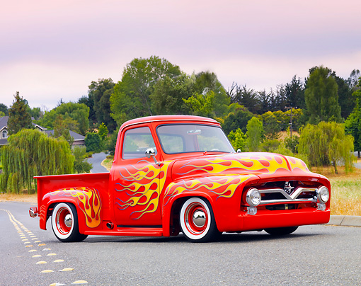 AUT 14 BK0041 01 © Kimball Stock 1954 Ford F-100 Pickup Truck Hot Rod Red With Flames 3/4 Front View On Pavement By Trees