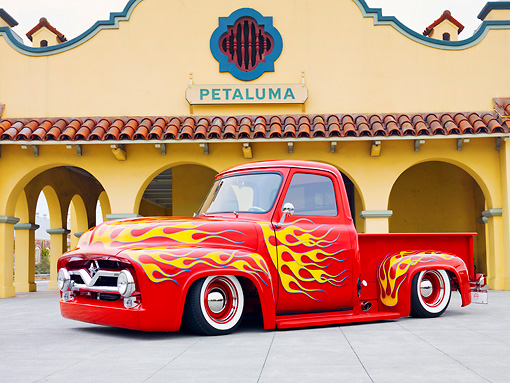 AUT 14 BK0042 01 © Kimball Stock 1954 Ford F-100 Pickup Truck Hot Rod Red With Flames 3/4 Front View On Pavement By Building