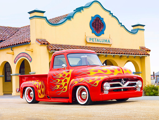 AUT 14 BK0043 01 © Kimball Stock 1954 Ford F-100 Pickup Truck Hot Rod Red With Flames 3/4 Front View On Pavement By Building