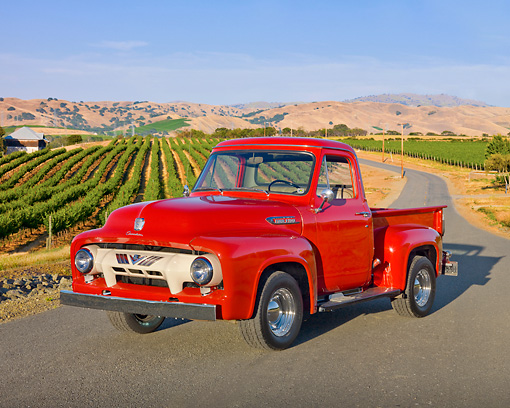 AUT 14 BK0044 01 © Kimball Stock 1954 Ford F-100 Pickup Truck Red 3/4 Front View On Pavement By Crops