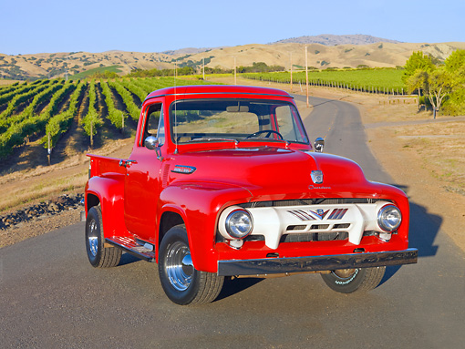 AUT 14 BK0045 01 © Kimball Stock 1954 Ford F-100 Pickup Truck Red 3/4 Front View On Pavement By Crops
