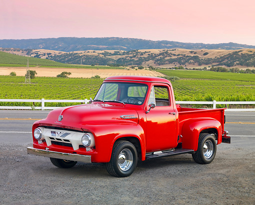 AUT 14 BK0046 01 © Kimball Stock 1954 Ford F-100 Pickup Truck Red 3/4 Front View On Pavement By Crops
