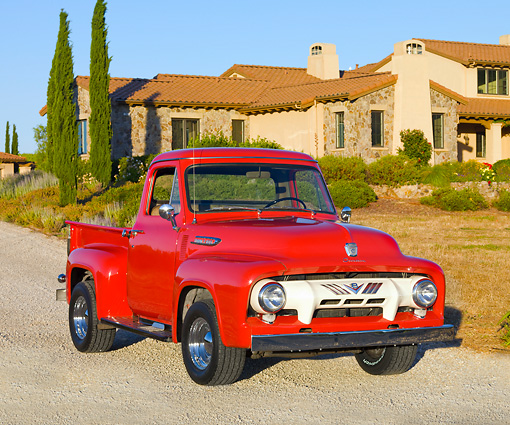 AUT 14 BK0048 01 © Kimball Stock 1954 Ford F-100 Pickup Truck Red 3/4 Front View On Gravel By House