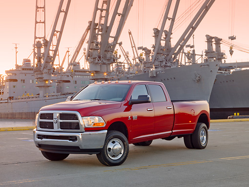 AUT 14 BK0055 01 © Kimball Stock 2010 Dodge Ram 3500 Pickup Truck Red 3/4 Front View On Dock By Ships At Dusk