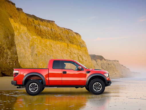 AUT 14 BK0058 01 © Kimball Stock 2011 Ford F-150 SVT Raptor Pickup Truck Red Profile View On Beach By Cliffs
