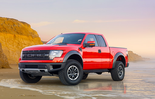 AUT 14 BK0059 01 © Kimball Stock 2011 Ford F-150 SVT Raptor Pickup Truck Red 3/4 Front View On Beach By Cliffs