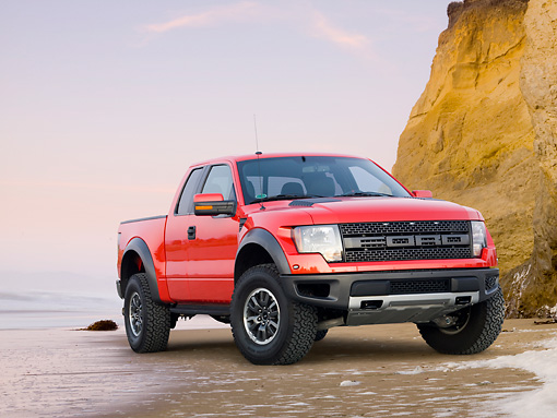 AUT 14 BK0060 01 © Kimball Stock 2011 Ford F-150 SVT Raptor Pickup Truck Red 3/4 Front View On Beach By Cliffs