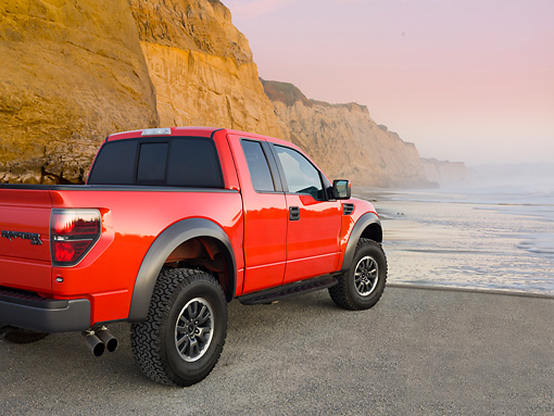 AUT 14 BK0061 01 © Kimball Stock 2011 Ford F-150 SVT Raptor Pickup Truck Red 3/4 Rear View On Beach By Cliffs