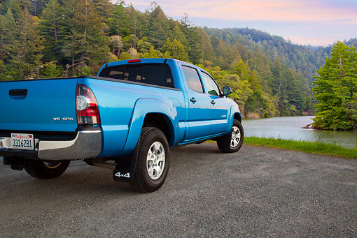 AUT 14 BK0072 01 © Kimball Stock 2011 Toyota Tacoma Double Cab Pickup Truck Blue 3/4 Rear View On Gravel By River In Forest