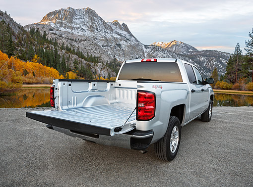 AUT 14 BK0095 01 © Kimball Stock 2014 Chevrolet Silverado Pickup Silver 3/4 Rear View On Gravel By Water And Mountains