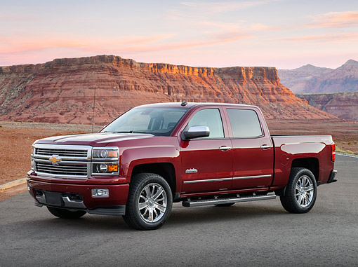 AUT 14 BK0099 01 © Kimball Stock 2014 Chevrolet Silverado Pickup Red 3/4 Side View On Pavement By Red Rock At Sunrise
