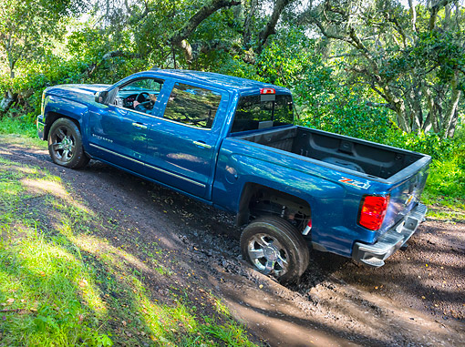 AUT 14 BK0103 01 © Kimball Stock 2015 Chevrolet Silverado 1500 Z71 4WD LTZ Crew Pickup 3/4 Rear View Driving In Mud