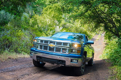 AUT 14 BK0105 01 © Kimball Stock 2015 Chevrolet Silverado 1500 Z71 4WD LTZ Crew Pickup 3/4 Front View Driving Through Forest