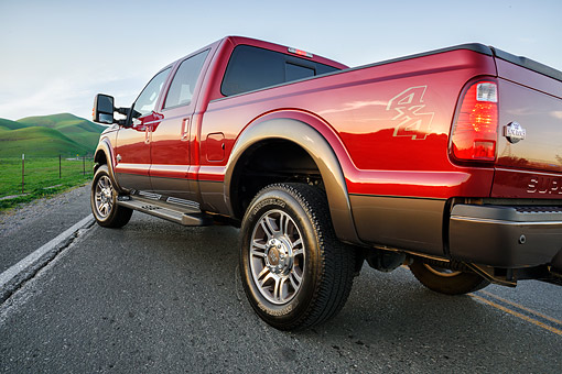 AUT 14 BK0120 01 © Kimball Stock 2015 Ford Super Duty F-350 Lariat Pickup Red 3/4 Rear View By Trees And Mountains