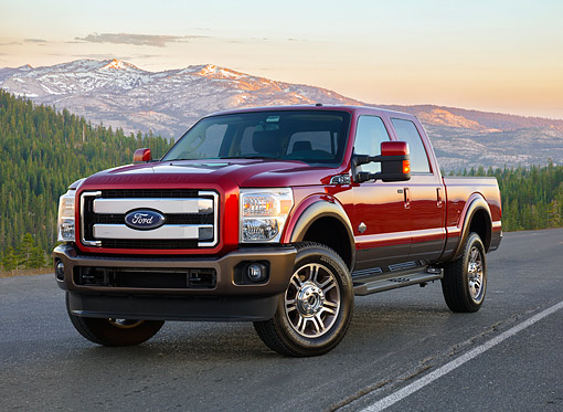 AUT 14 BK0122 01 © Kimball Stock 2015 Ford Super Duty F-350 Lariat Pickup Red 3/4 Front View By Trees And Mountains
