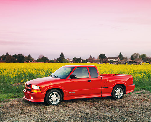 AUT 14 RK0075 03 © Kimball Stock 1999 Chevrolet S-10 Extreme Pick Up Truck Red 3/4 Side View On Yellow Flower Field At Dusk