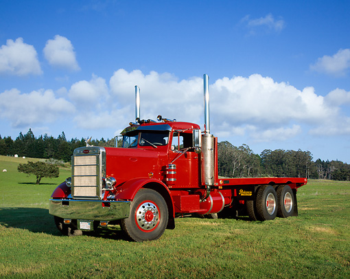 AUT 14 RK0079 01 © Kimball Stock 1965 Peterbilt Model 351 Red Truck 3/4 Side View On Grass By Trees Blue Sky