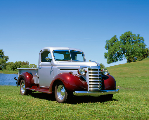 AUT 14 RK0085 01 © Kimball Stock 1940 Chevrolet 1/2 Ton Truck Silver And Maroon 3/4 Front View On Grass By Water