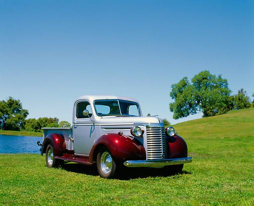 AUT 14 RK0085 02 © Kimball Stock 1940 Chevrolet 1/2 Ton Truck Silver And Maroon 3/4 Front View On Grass By Water