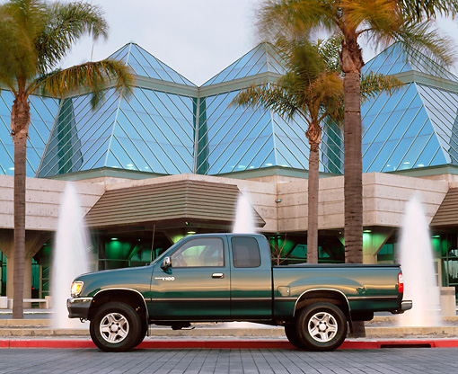 AUT 14 RK0217 09 © Kimball Stock 1997 Toyota T-100 Truck Green Profile On Pavement By Water Fountain