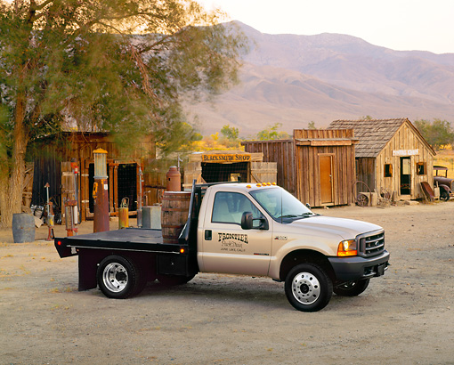 AUT 14 RK0283 03 © Kimball Stock 1999 Ford F550 Flatbed Truck Champagne 3/4 Side View On Dirt
