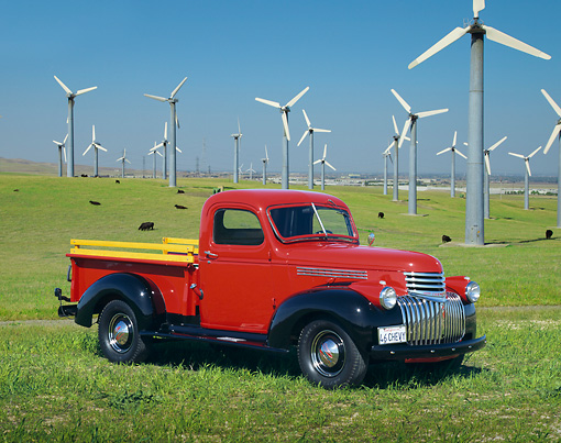 AUT 14 RK0382 04 © Kimball Stock 1946 Chevy Pick Up Truck Red Side 3/4 View On Grass By Windmills