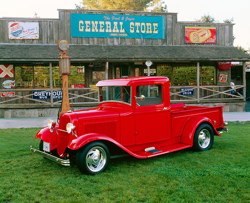 AUT 14 RK0438 02 © Kimball Stock 1933 Ford Pickup Truck Red Side 3/4 View On Grass By Store