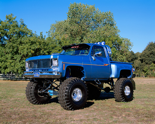 AUT 14 RK0441 02 © Kimball Stock 1976 GMC 4x4 Pickup Truck Blue 3/4 Side View On Grass By Trees