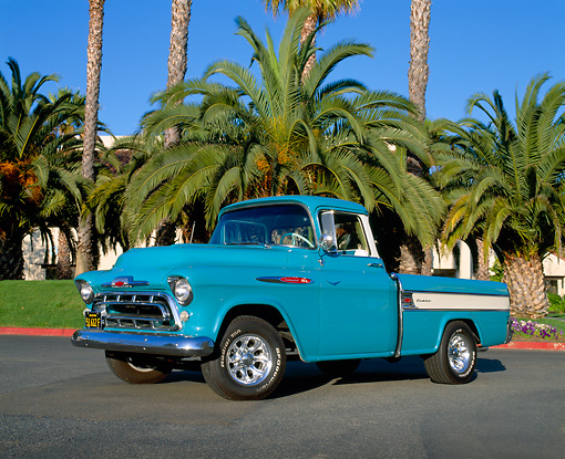 AUT 14 RK0496 04 © Kimball Stock 1957 Chevy Cameo Pick Up Truck Blue Low 3/4 Side View On Pavement By Palm Trees Blue Sky