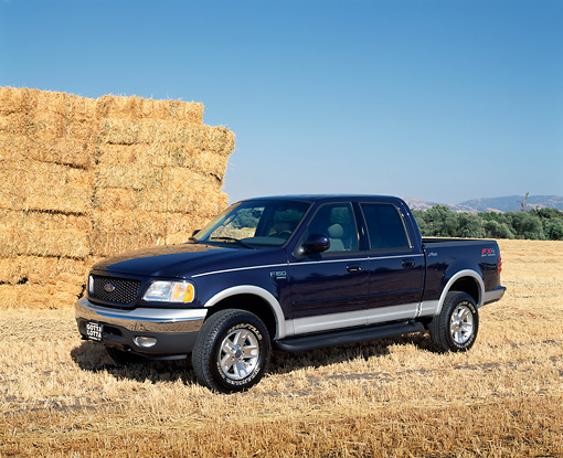 AUT 14 RK0711 02 © Kimball Stock 2002 Ford F-150 Lariat Blue Front 3/4 View On Dry Grass By Hay