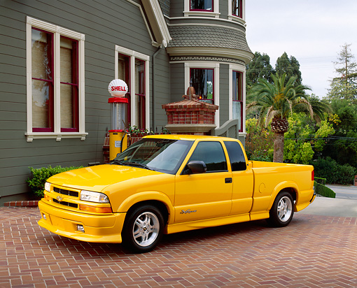 AUT 14 RK0879 03 © Kimball Stock 2003 Chevrolet Extreme S10 Yellow Truck 3/4 Side View On Pavement By House