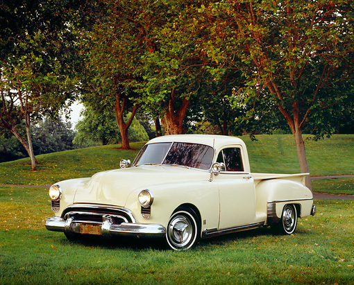 AUT 14 RK0994 01 © Kimball Stock 1949 Oldsmobile Pickup Truck Beige 3/4 Front View On Grass By Trees