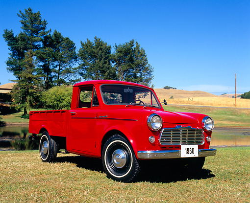 AUT 14 RK1024 03 © Kimball Stock 1960 Datsun Pickup Truck Red 3/4 Front View On Grass By Water And Trees