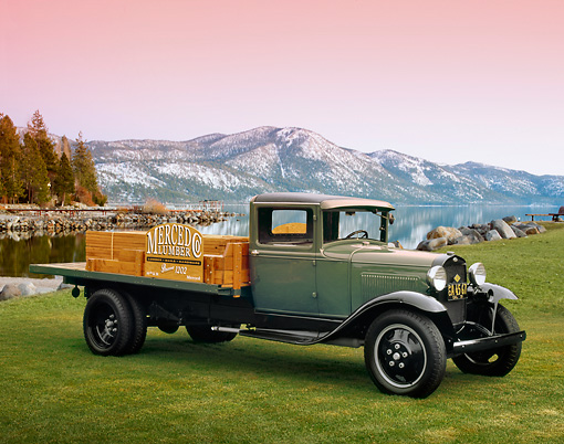 AUT 14 RK1034 01 © Kimball Stock 1931 Ford Model AA Truck Green And Black 3/4 Front View On Grass By Lake And Mountains