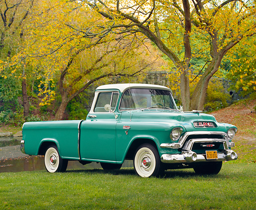 AUT 14 RK1072 02 © Kimball Stock 1956 GMC Suburban Pick Up Truck Green And White 3/4 Side View On Grass By Pond And Trees