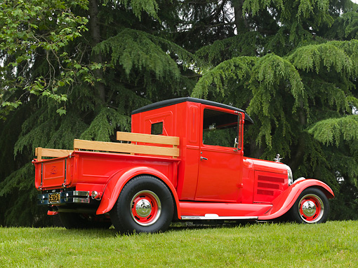 AUT 14 RK1143 01 © Kimball Stock 1928 Ford Model A Pick Up Truck Orange 3/4 Rear View On Grass By Trees
