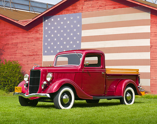 AUT 14 RK1148 01 © Kimball Stock 1936 Ford Pick Up Truck Red 3/4 Side View On Grass By Barn With American Flag