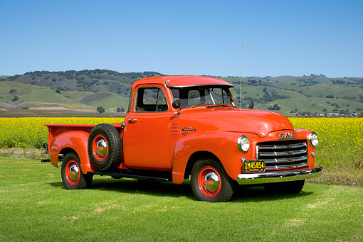 AUT 14 RK1196 01 © Kimball Stock 1953 GMC 3/4 Ton Pick Up Truck Red 3/4 Side View On Grass By Wildflowers And Hills