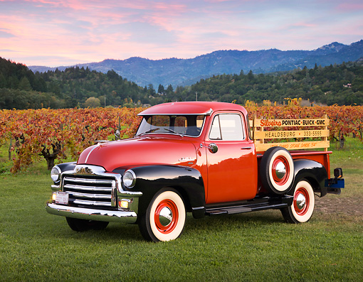 AUT 14 RK1220 01 © Kimball Stock 1954 GMC Hydramatic 100 Pick Up Truck Red And Black 3/4 Side View On Grass By Crops At Dusk