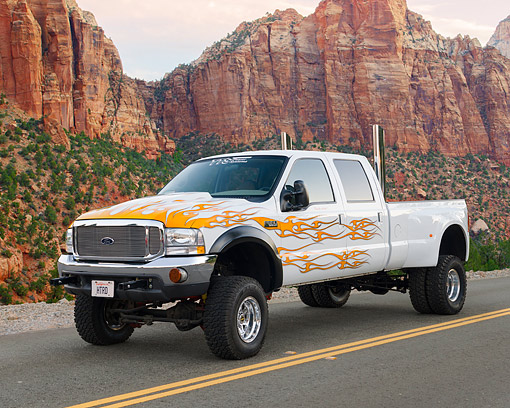 AUT 14 RK1222 01 © Kimball Stock 2000 Ford F-350 White With Flames Dually 3/4 Side View On Pavement By Red Rock